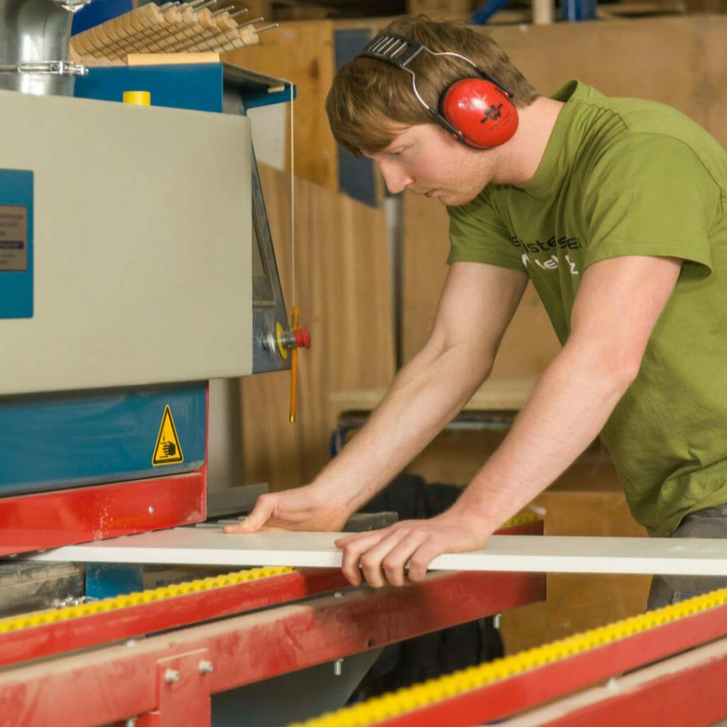 Bauteile werden in eine Kantenbearbeitungszentrum eingeführt und an der Schmalfläche beschichtet
