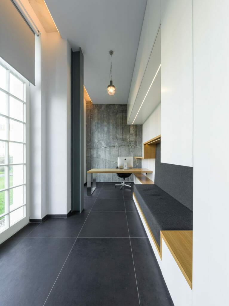 modernes Arbeitszimmer in einem schmalen Raum mit Sitzbereich und Gästebettfunktion, Stauraumschränke und indirekter Beleuchtung