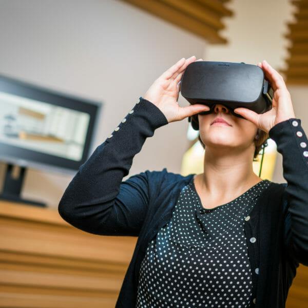 eine Frau betrachtet Ihre zukünftige Einrichtung mit einer VR-Brille