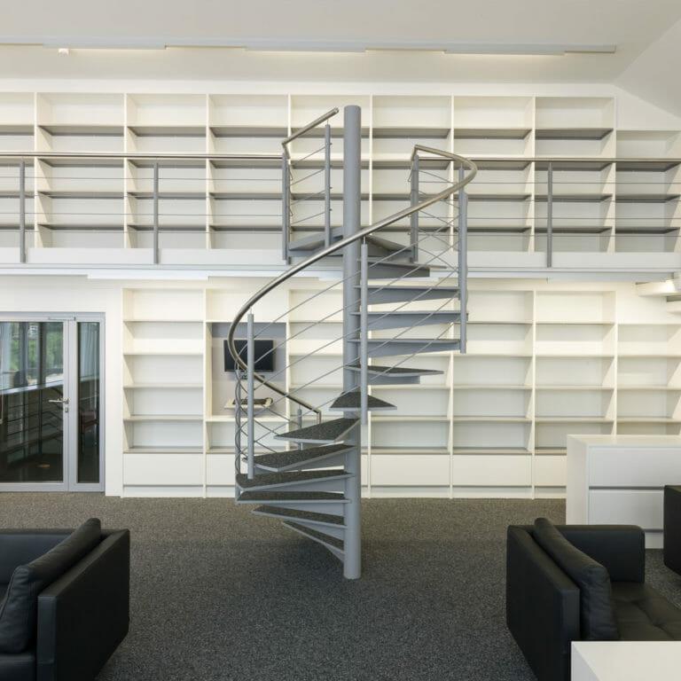 Bibliothek mit Bücherregalen auf zwei Ebenen mit Wendeltreppe