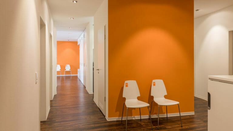 Wartebereich im Flur mit orange aktzentuierten Wänden