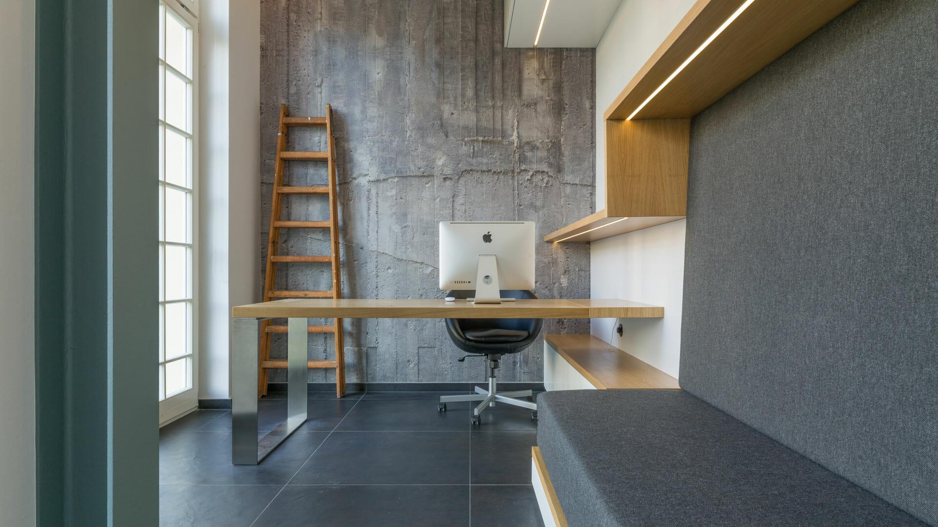 Arbeitszimmer in Grautönen, Beton und Eiche mit Ausziehcouch