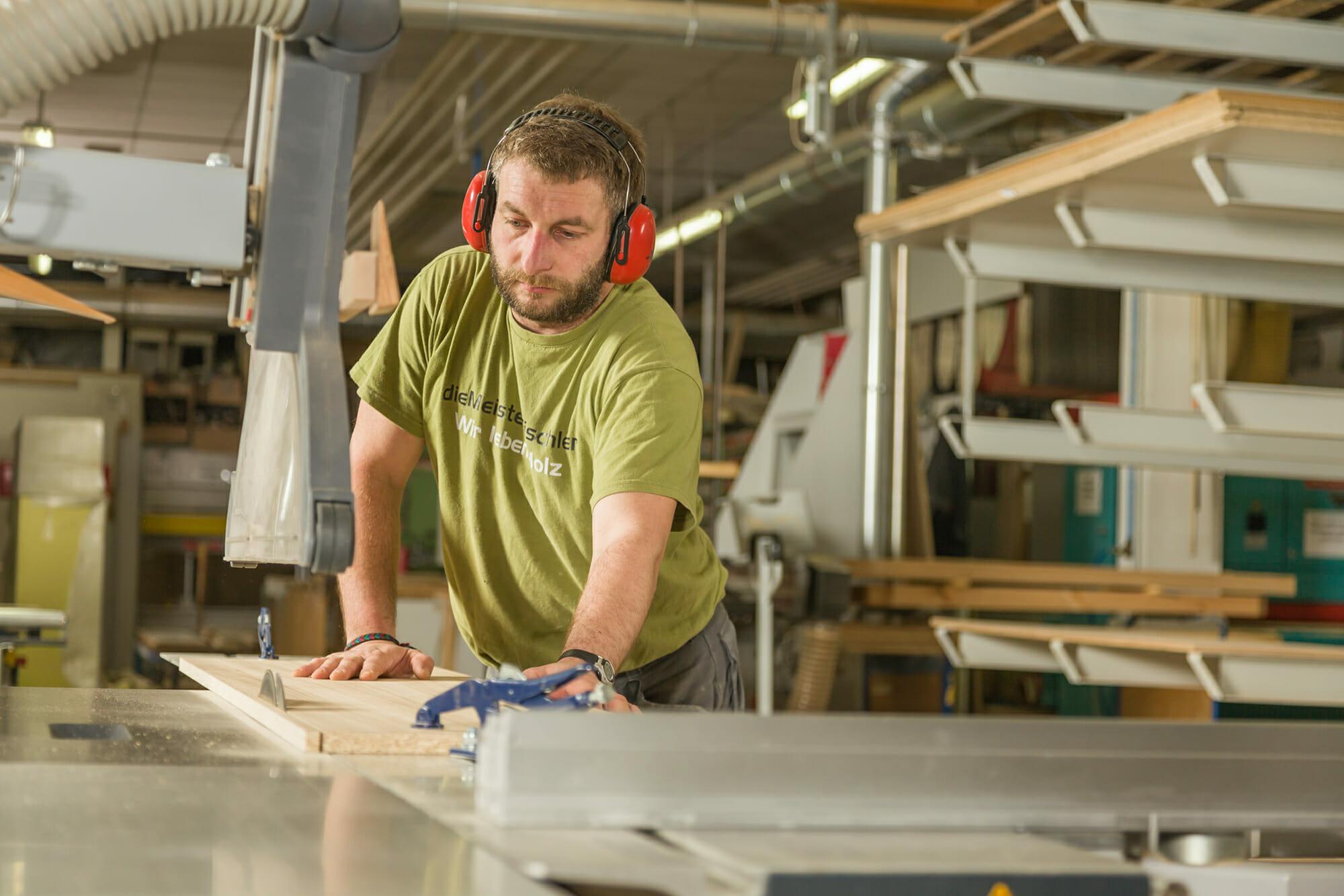 ein Mitarbeiter sägt an einer Formatkreissäge ein Bauteil auf Maß