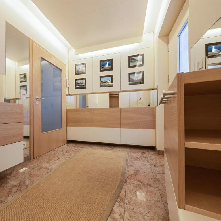 Stauraummöbel mit Bilderfronten und Spiegelniesche in weiß und mit Holzaktzenten