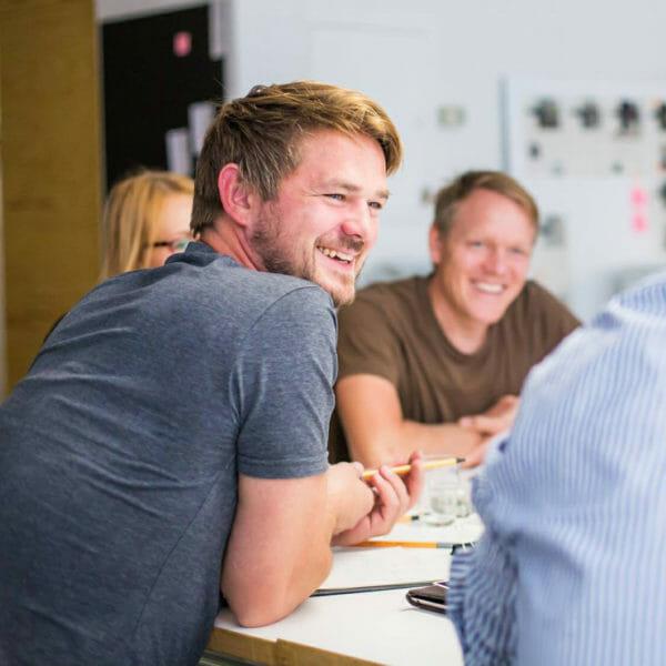 David Oehme, lächelnd sitzend am Tisch mit anderen Personen
