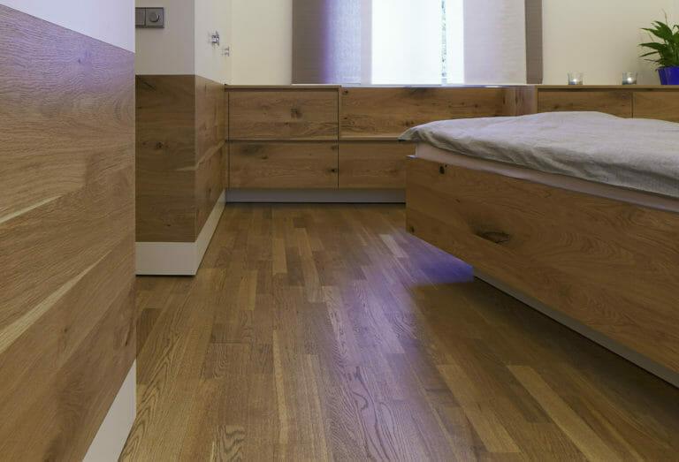 einzigartige Schlafzimmer Einrichtung mit schrägem Bett, Fronten Eiche Starkfurnier kombiniert mit weißem Lack und integriertem Sitzbereich