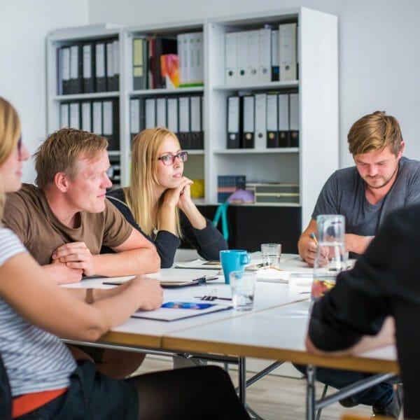 das Team dieMeisterTischler sitzend an einem Tisch bei einem workshop
