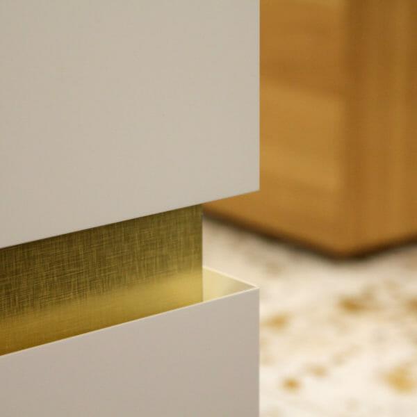 Detail einer Grifffuge mit Fronten auf Gehrung, goldfarben hinterlegt