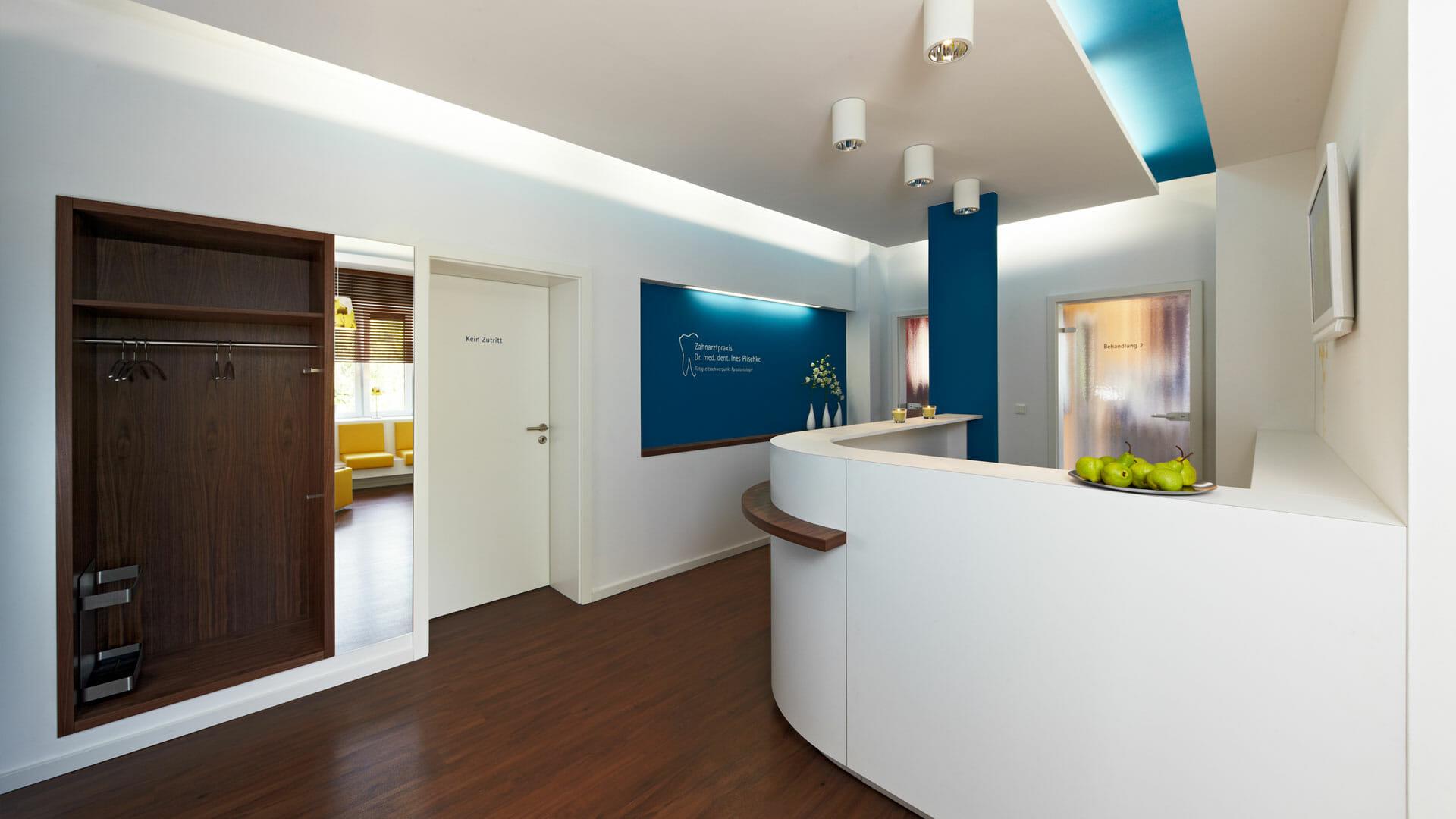 modern gestalteter Empfangsbereich mit dunklem Holz und blauen Aktzenten