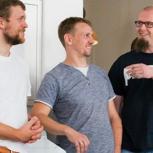 Jan Wrobel, lächelnd mittig von 2 anderen Personen bei einem workshop