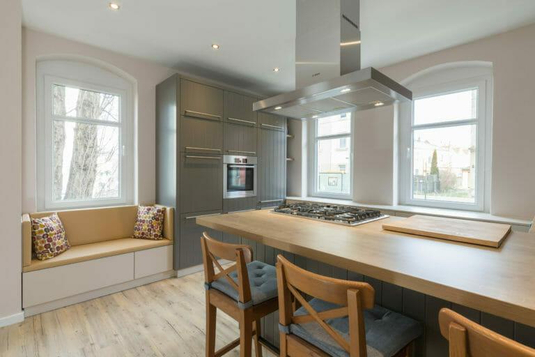 Küche mit großer mittiger Kochinsel und integriertem Sitzplatz am Fenster