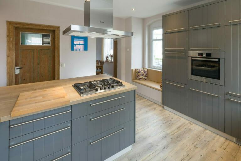 Landhausküche mit schlichten, grau lackierten Fronten mit senkrechten Fräsungen