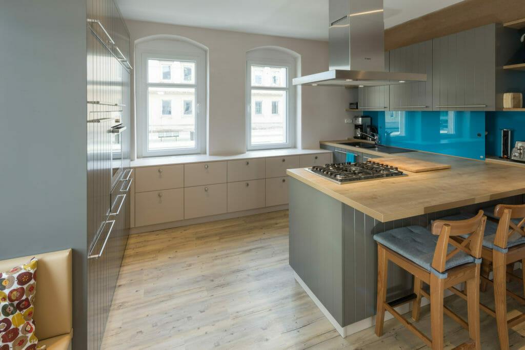 großzügige Landhausküche mit Hängeschränken und Nischenbereich mit verschiebbarer, petrolfarben lackierter Glasscheibe