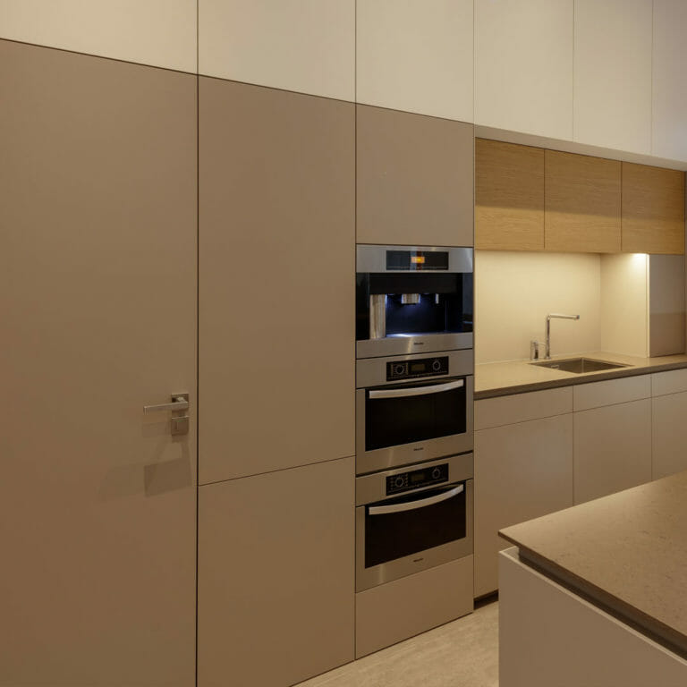 minimalistische, grifflose Hochschrankanlage mit rahmenlos integrierter Zimmertür