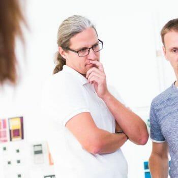Nico Deutschmann, mit weißem Shirt, Kopf leicht geneigt, Arme verschränkt, linke Hand vor dem Mund