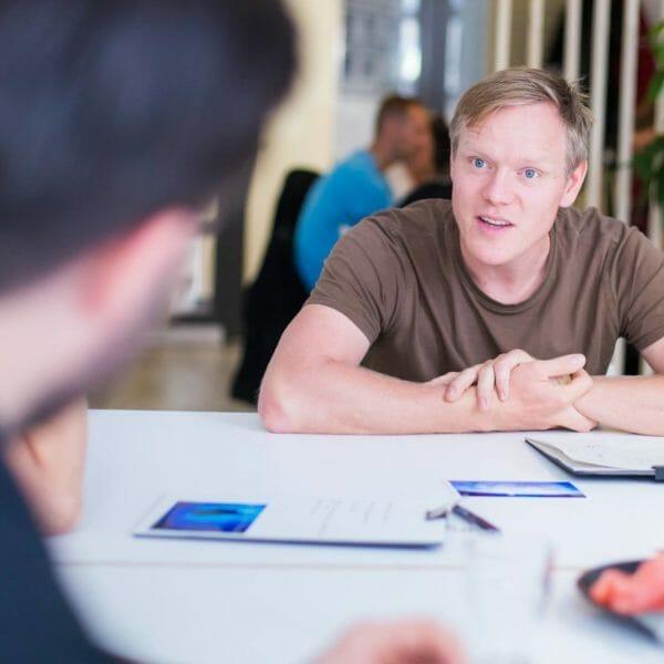 Robert Domaschk, sitzend am Tisch, im Gespräch
