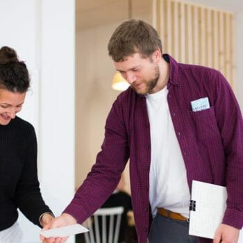 Robert Jähnen, leicht gebeugt mit einer Karte in der Hand im Gespräch