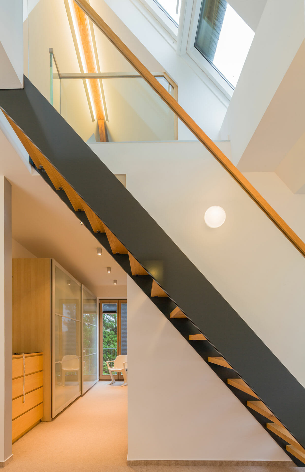 Innenausbau Dachgeschoss mit minimalistischer Treppe aus Stahl, Holz und Glas