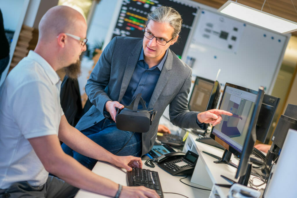 Nico Deutschmann in Absprache mit einem Mitarbeiter über Virtual Reality am PC