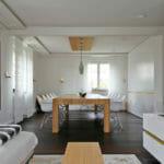 moderner Wohn und Esszimmerbereich, mit großem Eichenholztisch, weiß lackierten Designer Einbaumöbeln