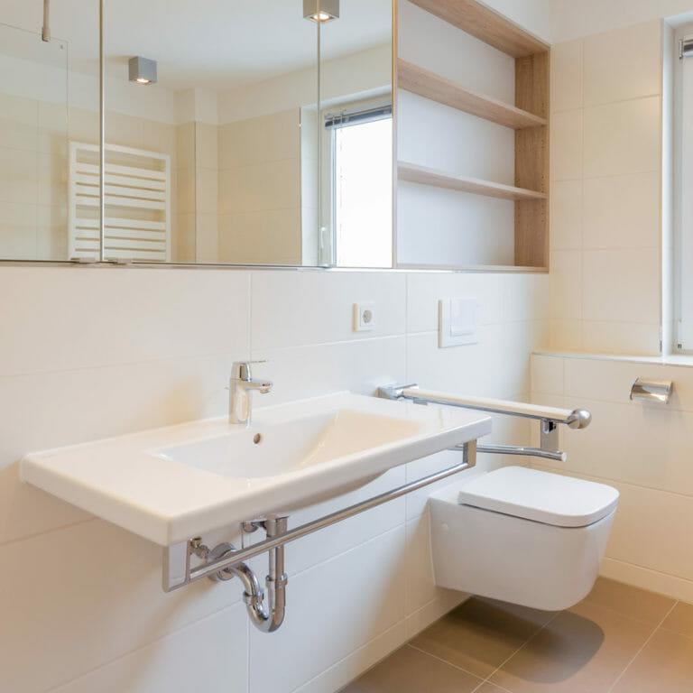barrierefreies Waschbecken und WC, darüber auf gesammter Raumbreite Spiegelschrank und Regal