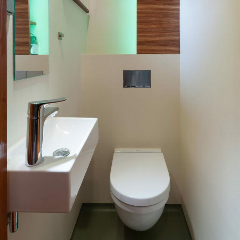 Stauraumregal in Zebrano Furnier mit LED in Niesche oberhalb der Toilettenvorwandinstalation in Gäste WC