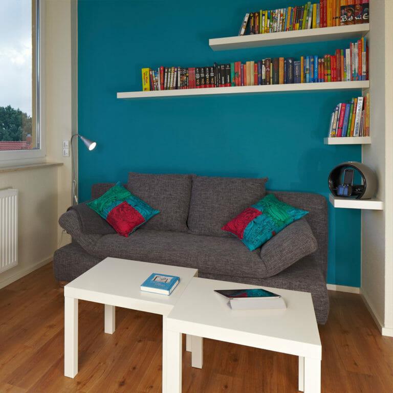 Leseecke mit Tablarböden als Bücherregal über Sofa